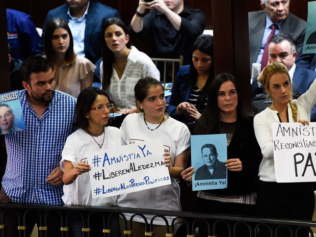 Lilian Tintori (à direita), mulher do opositor preso Leopoldo Lopez, e Eveling Trejo De Rosales (segunda à direita), mulher do ex-prefeito de Maracaibo Manuel Rosales, também preso, fazem protesto a favor da anistia antes da sessão da Assembleia Nacional  (Foto: AFP PHOTO/JUAN BARRETO)