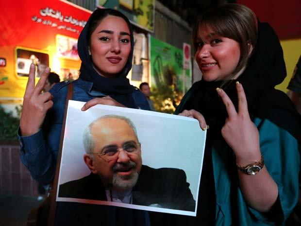 Mulheres seguram foto do ministro das Relações Exteriores do Irã, Javad Zarif, ao comemorar o acordo anunciado nesta terça-feira (14) (Foto: AFP PHOTO / ATTA KENARE)