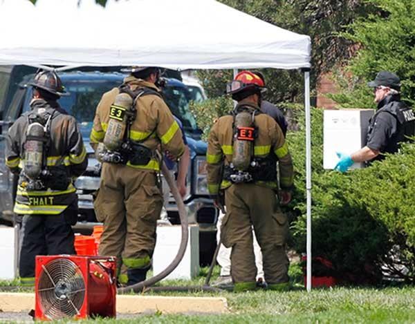 Junto a bombeiros, policial carrega caixa com químicos das armadilhas montadas no apartamento do atirador dos EUA (Foto: Ed Andrieski/AP)