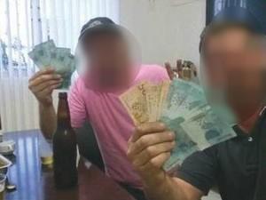 Em uma das fotos, dois homens aparecem com notas de dinheiro nas mãos (Foto: Reprodução/RBSTV)