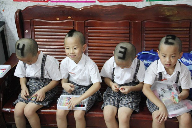 Pais decidiram marcá-los com os números 1, 2, 3, 4 em suas cabeças para tornar mais fácil para os professores e colegas distingui-los. (Foto: AFP)