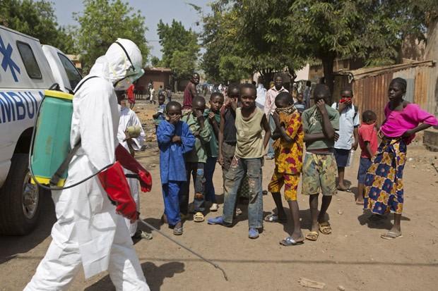 Crianças observam agente desinfetando local em Bamako, no Mali, dia 14 de novembro (Foto: Reuters/Joe Penney)