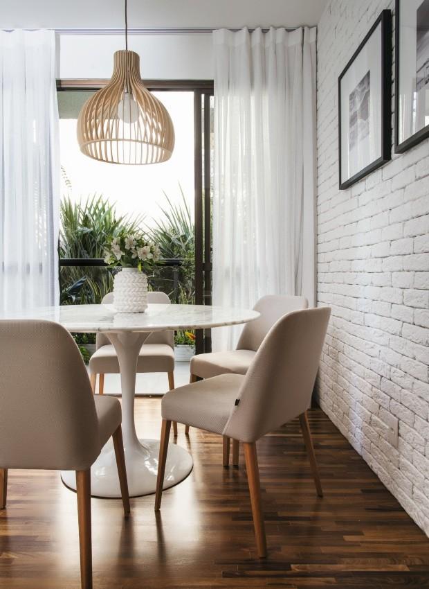 Sala de jantar. Sob o pendente da Lustres Yamamura estão a mesa Saarinen com vaso da Zara Home, cercada de cadeiras da Oppa. No piso, tacos-palito de cumaru (Foto: Cacá Bratke / Divulgação)