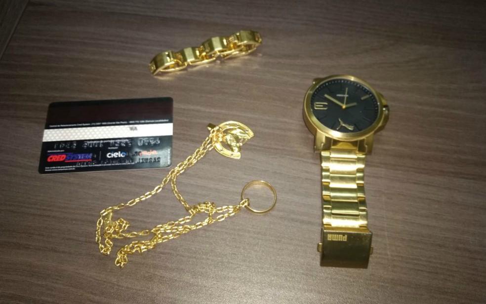 Objetos pessoais do empresário e cartão de crédito recuperados com suspeitos (Foto: Polícia Civil/ Divulgação)