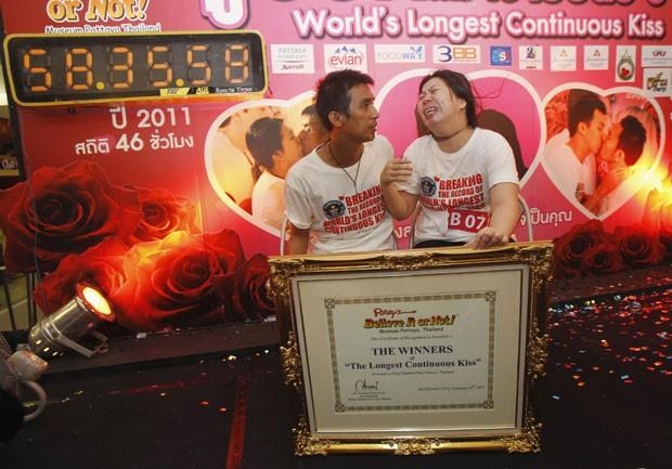 O casal tailandês celebra como novo detentor da marca de beijo contínuo mais longo já registrado, ao lado do cronômetro com a marca (Foto: Chaiwat Subprasom/Reuters)
