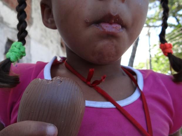 Menina que vive com a mãe pelas ruas de Maceió come chocolate doado por voluntários (Foto: Waldson Costa/G1)