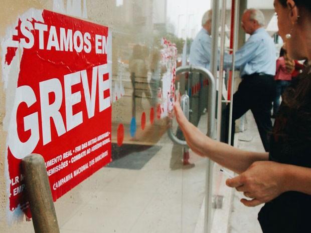 Funcionária retira adesivo referente a greve com o fim da paralisação (Foto: Marcelo Brandt/G1)