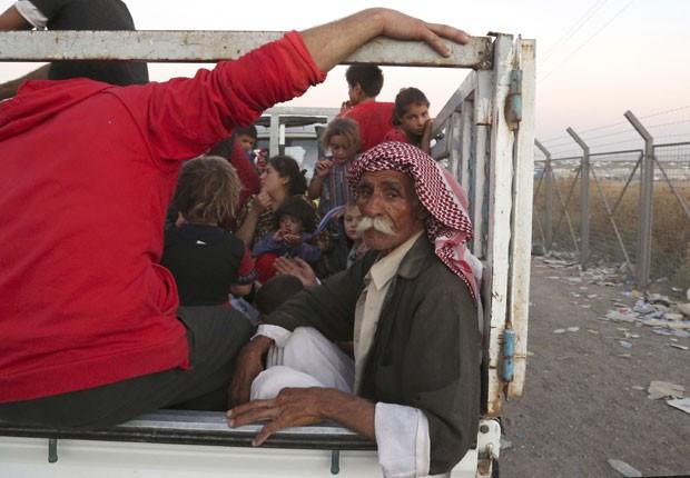 Membros da etnia Yazidi fogem para acampamento de Bajid Kandala, perto da fronteira com a Síria (Foto: Khalid Mohammed/AP)