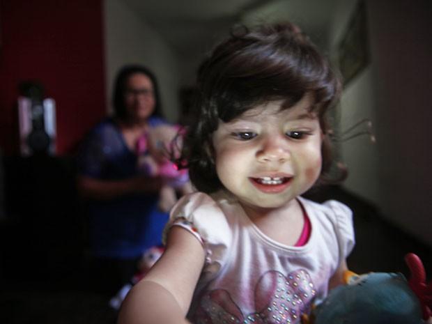 Letícia brinca sob olhar atento da avó Erika enquanto a mãe está trabalhando (Foto: Glauco Araújo/G1)