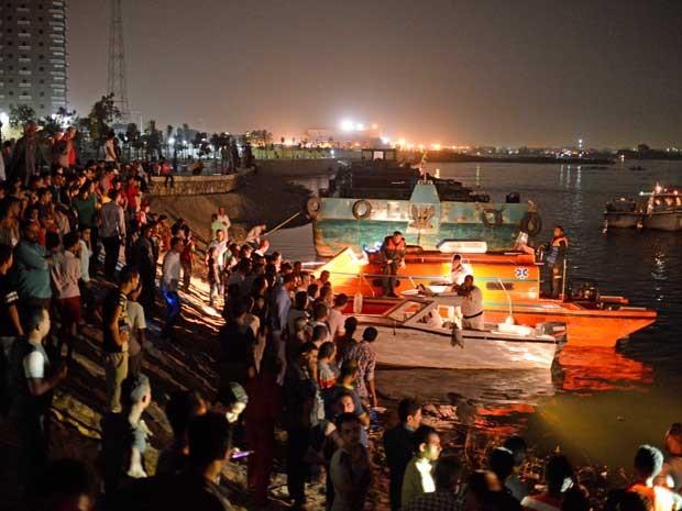 Pessoas à margem do Nilo, à espera de informações sobre colisão de barcos no Egito. Equipes de resgate ainda procuram por 4 desaparecidos. (Foto: AFP Photo)