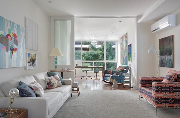 SALA DE ESTAR | O tapete, da Phenicia Concept, cobre todo o piso do ambiente. Sofá e poltrona da Decameron Design. As almofadas e o abajur já pertenciam ao acervo da família.   Luminária de chão, Bauhaus 90, à venda na Lumini (Foto: Denilson Machado - MCA Estúdio/Divulgação)