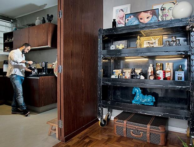 O stylist na cozinha, que segue   o estilo industrial. No corredor, o móvel de hospital comprado no antiquário À La Garçonne faz as vezes de bar e estante  (Foto:  )
