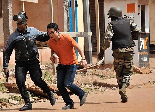 Policial acompanha refém resgatado do hotel Radisson Blu em Bamako (Foto: Habibou Kouyate/AFP)