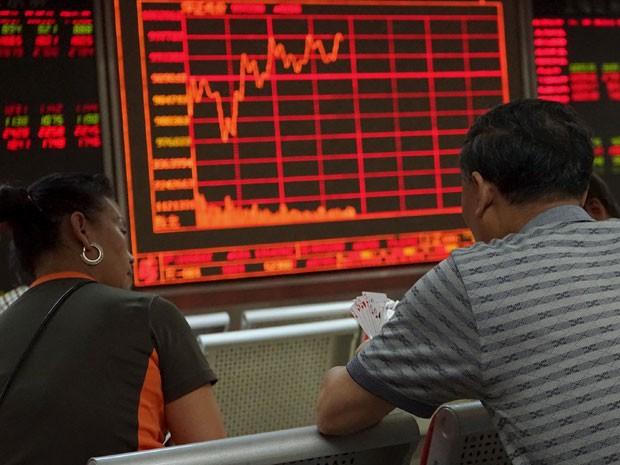 Investidores jogam cartas em frente a painel eletrônico em Pequim (Foto: Reuters)