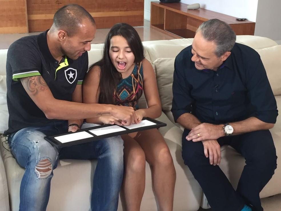 Descrição da imagem: filha de Roger sente o gol do pai no quadro em relevo, ao lado do atacante e de Luis Roberto (Foto: Felippe Costa)