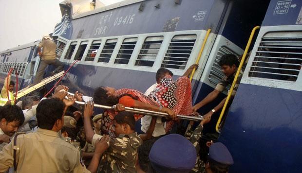 Mulher ferida é retirada de trem após acidente nesta terça-feira (22) na Índia (Foto: AP)