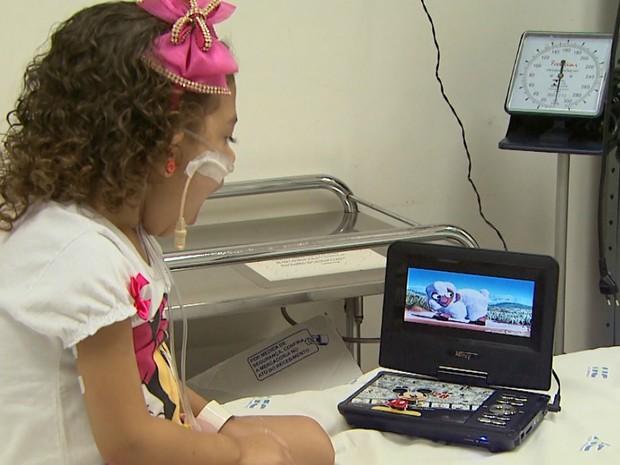 Vitória dos Santos, de 5 anos, se distrai assistindo aos filmes (Foto: Reprodução/EPTV)