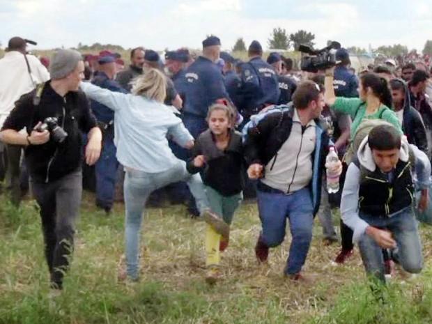 A cinegrafista Petra Laszlo, de uma TV húngara, causou indignação internacional ao chutar crianças refugiadas que tentavam escapar de um bloqueio na fronteira com a Sérvia. Filiada a um partido radical que faz campanha contra imigrantes, ela foi demitida (Foto: AFP/Index.hu)