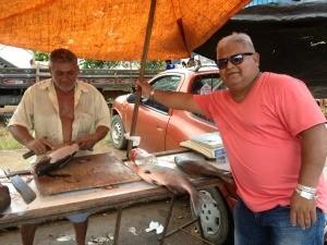 O feirante Raimundo limpa o peixe de Grecevaldo Guimarães (Foto: Ivanete Damasceno / G1)