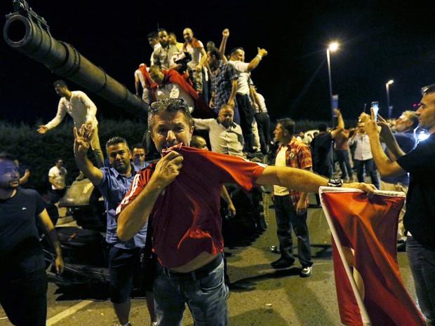 Pessoas sobem em um tanque do exército no aeroporto Ataturk, em Istambul (Foto: Reuters)