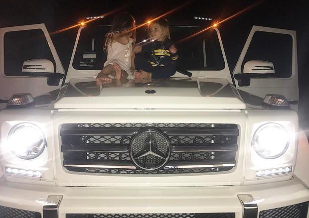 Penelope e Reign posam no carro de Kourtney Kardashian (Foto: Reprodução)