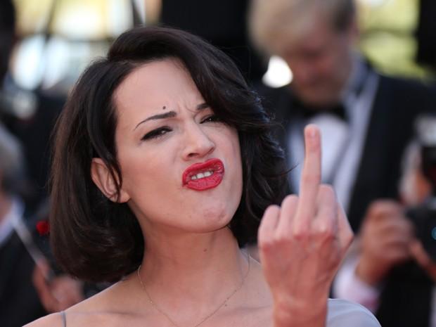 A atriz italiana Asia Argento faz gesto ofensivo para fotógrafos no tapete vermelho para o evento de exibição do filme 'Zulu'. O longa é o último a ser exibido no festival, que começou no dia 14 de maio e termina neste domingo (26), quando será conhecido  (Foto: AFP PHOTO / LOIC VENANCE )
