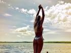 Ex-BBB Adriana se alonga, só de biquíni, de frente para lagoa