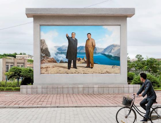 Um dos milhares de murais com o pai e o avô de Kim,os ditadotres anteriores.Apresentada  a estrangeiros,Pyongyang parece ser cuidadosamente preparada para indicar que tudo funciona  (Foto: Serie Red Ink 2017/Max Pinckers)