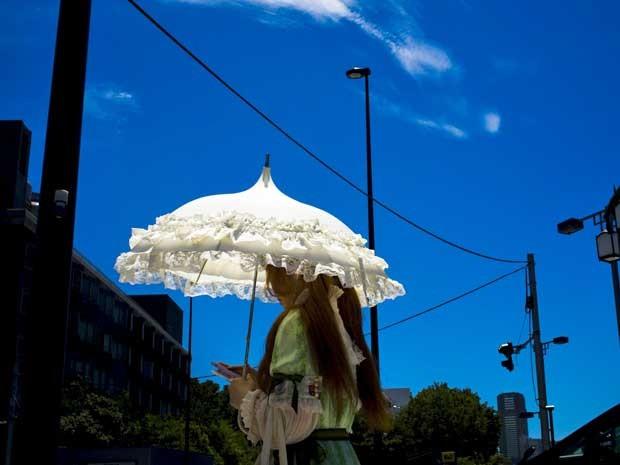 Mulher se protege do forte calor em Tóquio (Foto: Thomas Peter / Reuters)
