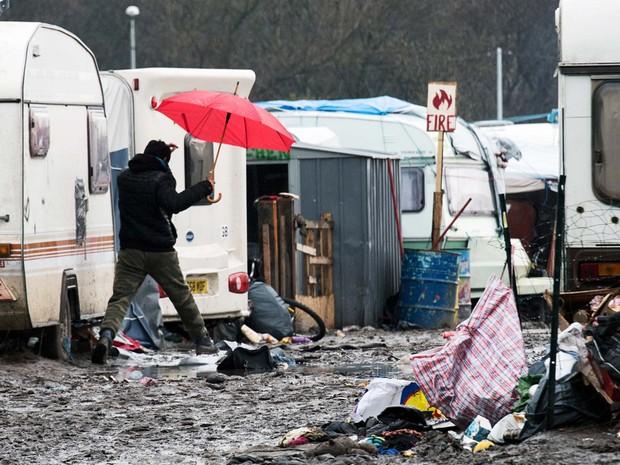 Homem caminha sob a chuva no campo de refugiados conhecido como 'Selva' em Calais, na França (Foto: DENIS CHARLET / AFP)