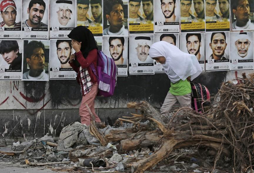 Crianças caminham até a escola em Malkiya, Bahrein. No muro, fotos de desaparecidos e mortos em protestos pró-democracia no país