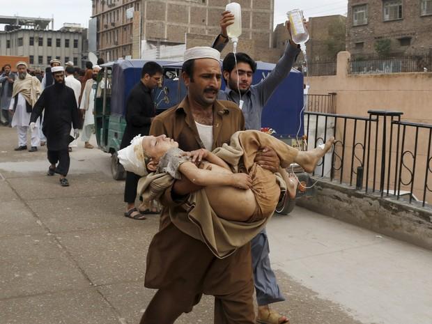 Um homem carrega um menino ferido até o hospital Lady Reading em Peshwar, no Paquistão, após forte terremoto na região (Foto: Mohammad Sajjad/AP)