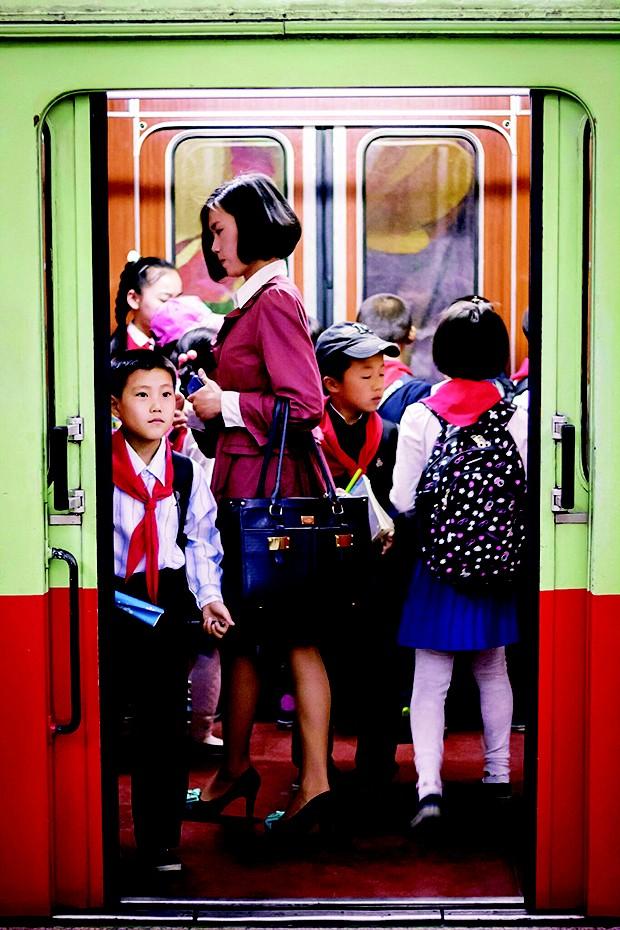 Norte-coreana no metrô usa réplica de uma bolsa de grife. As cópias entram no país pela China (Foto: Shane Horan)