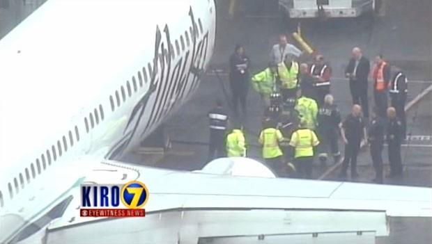 Funcionário da Menzies Aviation é retirado da área de carga de avião da Alaska Airlines nesta segunda-feira (13) após a aeronave realizar um pouso de emergência (Foto: KIRO 7 via AP)