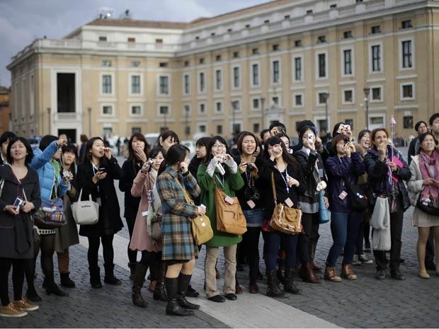 Turistas tiram fotos na Praça de São Pedro, no Vaticano, nesta segunda-feira (11) (Foto: AFP)