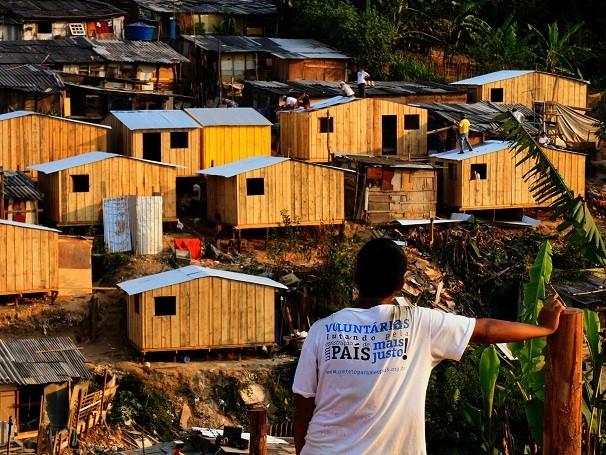 Mulher observa casas construidas pela ONG Teto em comunidade de São Paulo (Foto: Divulgação/ONG Teto)