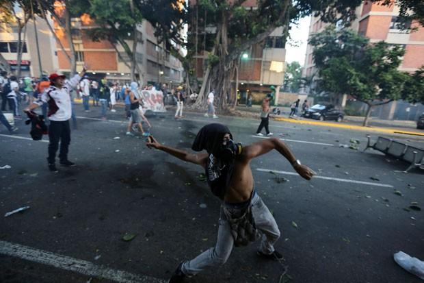 Manifestante joga pedra contra a polícia durante protestos em Caracas (Foto: Fernando Llano/AP)