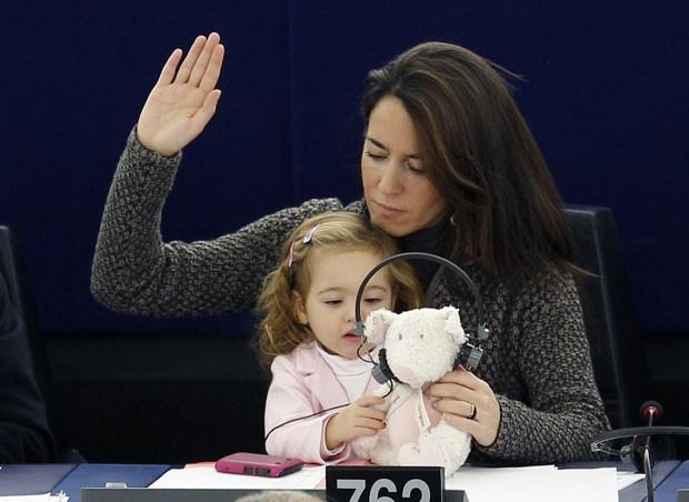 Menina chegou a pôr o ursinho para 'ouvir' a tradução simultânea (Foto: Vincent Kessler/Reuters)