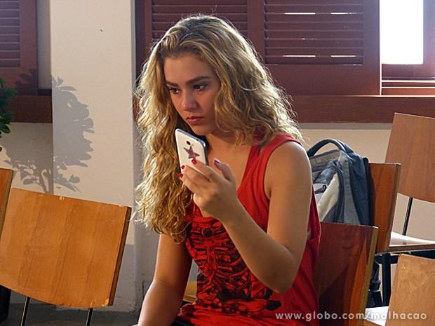 Meg recebe ligação dos States e fica sabendo que a mãe está presa (Foto: Malhação / TV Globo)