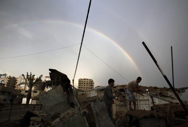 Palestinos inspecionam nesta sexta-feira (23) casa destruída por bombardeio em Gaza (Foto: AFP)