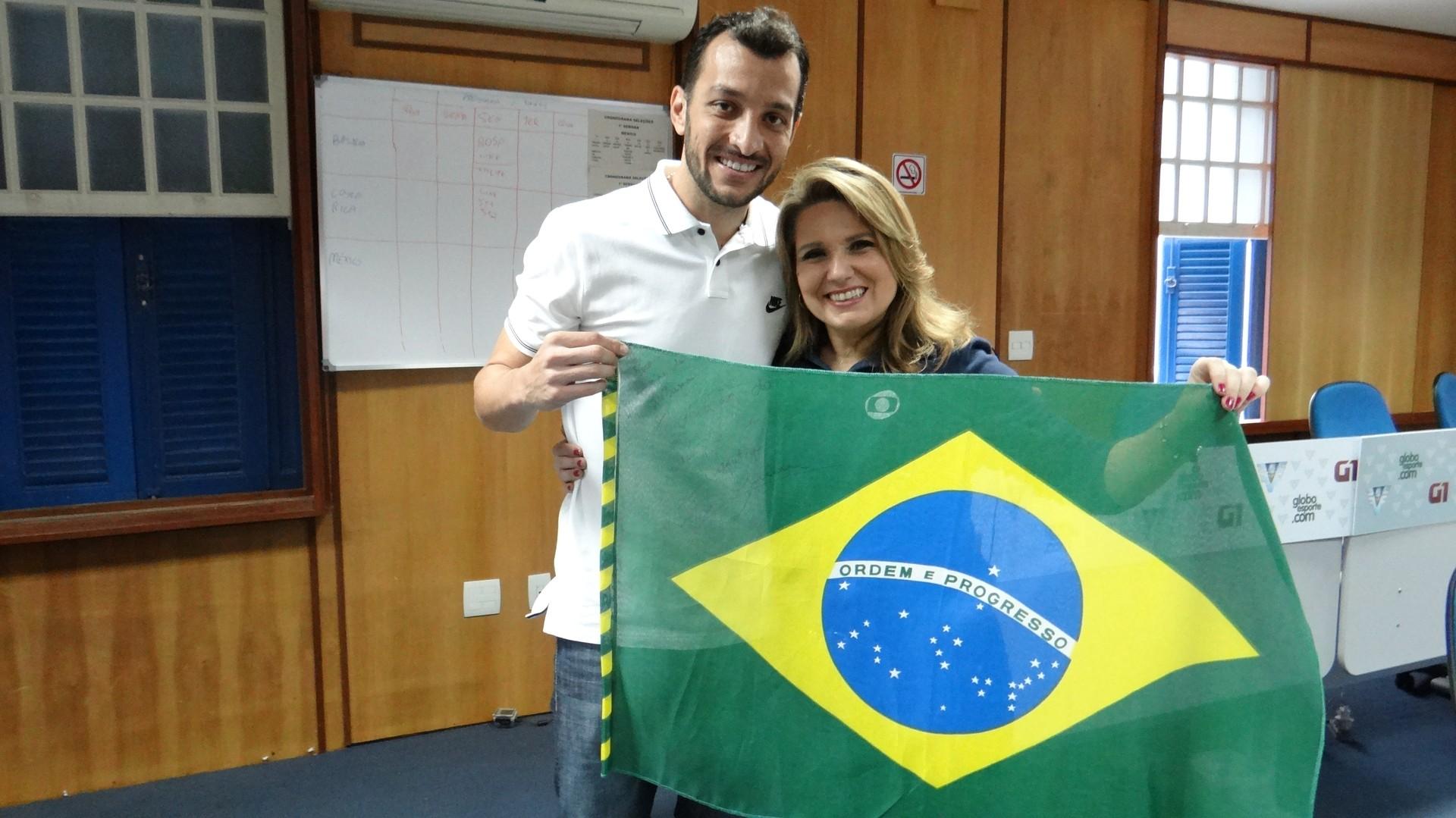 Edu Dracena e Vanessa Faro segurando a bandeira do Brasil autografada (Foto: Priscila Martinez)