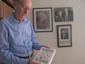 O ex-deputado Carlos Murilo, em sua casa, em Brasília, com exemplar do livro que escreveu sobre JK (Foto: Laura Tizzo / G1)