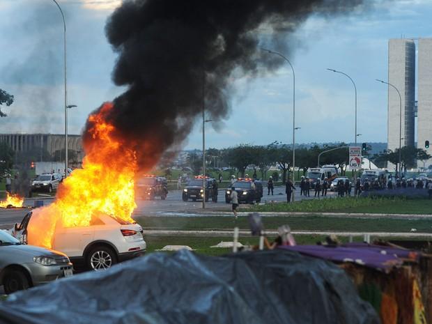 Um carro em chamas é visto durante um protesto na Esplanada dos Ministérios, em Brasília, contra a PEC 55, que limita os gastos públicos para os próximos 20 anos (Foto: Andressa Anholete/AFP)