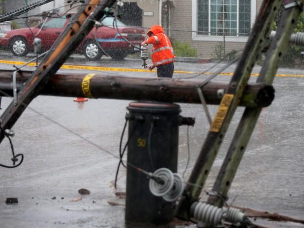 Funcionário recolhe cabos de energia após a queda de um poste em San Leandro, na Califórnia  (Foto: AP Photo/Bay Area News Group, Aric Crabb)