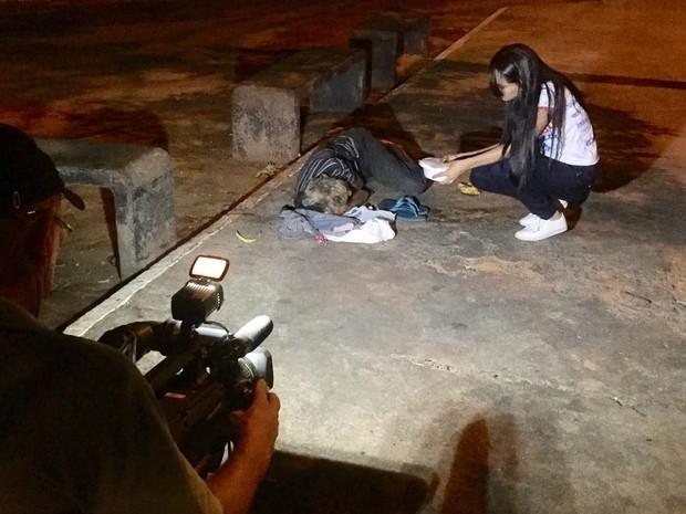 Voluntária dá comida a morador de rua, durante ação em Gurupi (Foto: Heitor Moreira/TV Anhanguera)