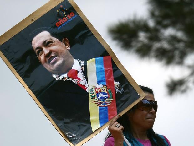 Mulher carrega cartaz com foto de Hugo Chavez (Foto: Juan Barreto/AFP)