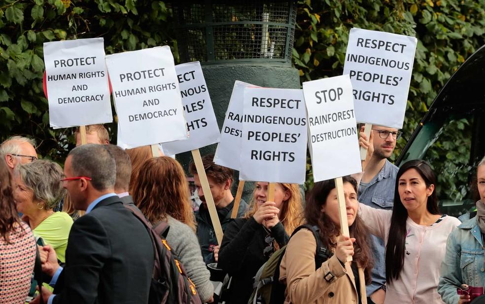 Um grupo fez uma manifestação em Oslo, na frente do prédio onde Temer e Erna, exibindo cartazes sobre democracia, direitos humanos e indígenas. (Foto: Håkon Mosvold Larsen / NTB scanpix / AFP Photo)