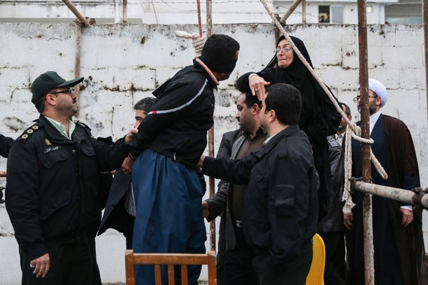 """A mãe do jovem assassinado por Balal Abdullah dá um tapa em seu rosto antes dele ser enforcado. O Irã segue a regra do """"olho por olho"""": no caso de assassinato, parentes da vítima têm o direito de reclamar a execução do assassino (Foto: Arash Khamooshi/Isna/AFP)"""