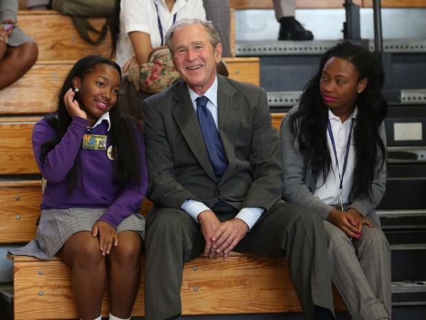 O ex-presidente dos EUA, George W. Bush, se senta entre as estudantes Ashantae Martin (esquerda) e Ronjae Pleasant durante evento na Warren Easton High School, em Nova Orleans, na sexta (28) (Foto: Joe Raedle/Getty Images/AFP)