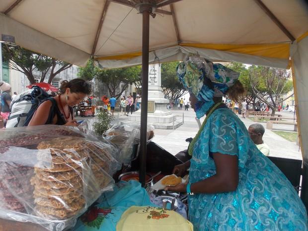 Baiana Mary atendendo a cliente turista na Cruz Caída, no Pelourinho. (Foto: Denise Paixão/G1)
